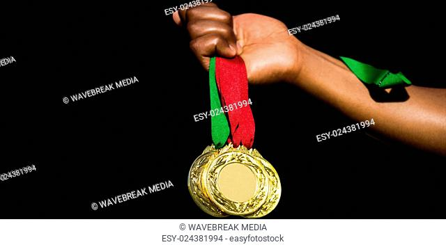 Hand holding three gold medals on white background