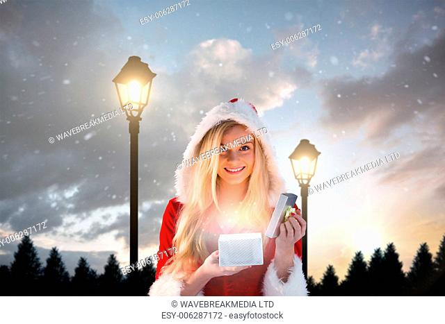 Sexy santa girl opening gift against lampposts at night