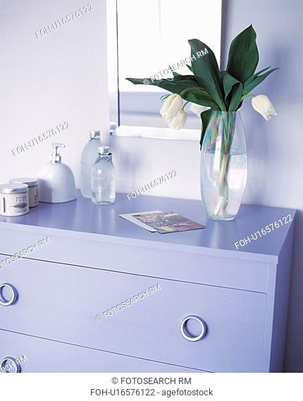 Glass vase of white tulips on top of a lilac painted chest of drawers