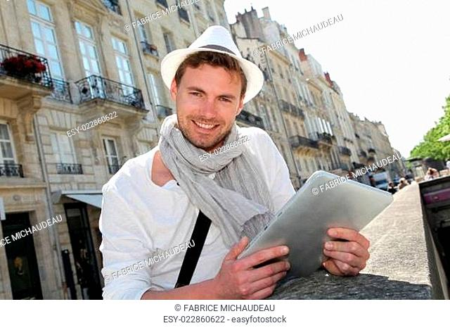 Young man with hat in town using electronic tablet