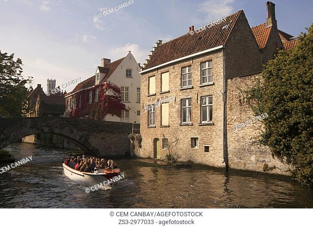 Tourists on the boat during a trip near a bridge on the canal, Bruges, West Flanders, Belgium, Europe