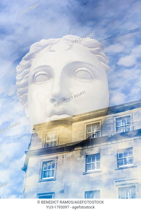 Reflection of building on classical style mask in shop window, High Street, Oxford, England, UK
