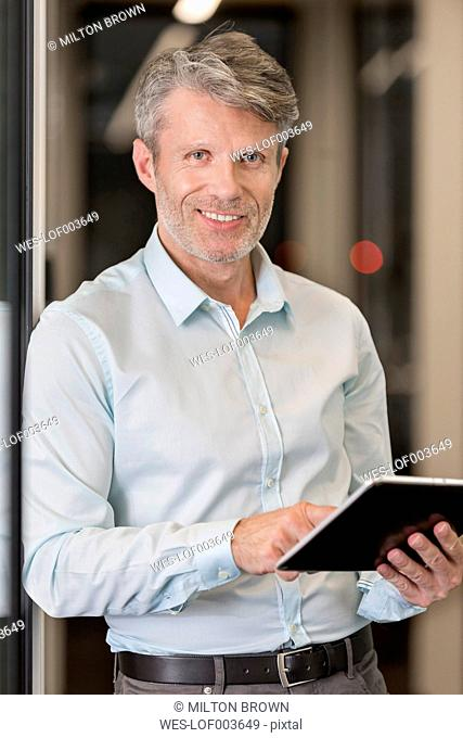 Mature businessman standing in office corridor using digital tablet