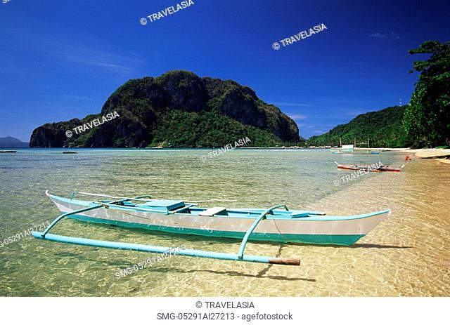 Philippines,Palawan,Bascuit Bay,El Nido,Outrigger on Tropical Beach at Sunset