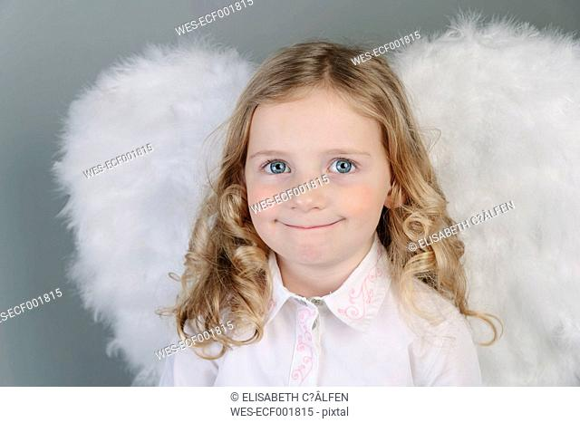 Portrait of blond little girl with angel wings