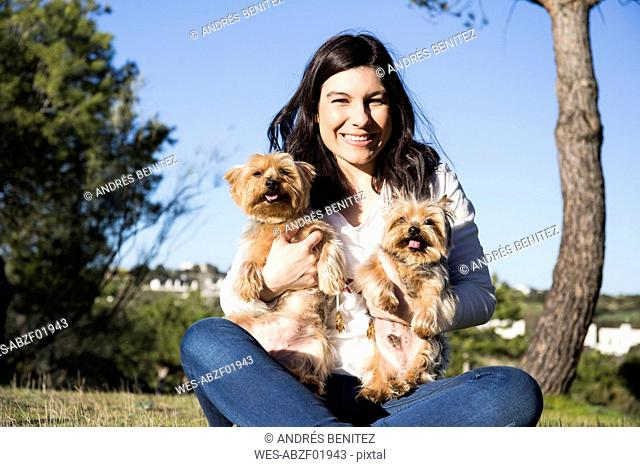 Portrait of happy young woman sitting with her Yorkshire Terriers on a meadow