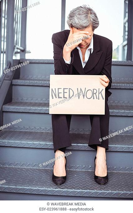 Unemployed businesswoman with need work placard