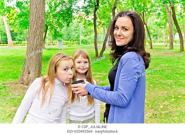 Woman with two girls drinking tea