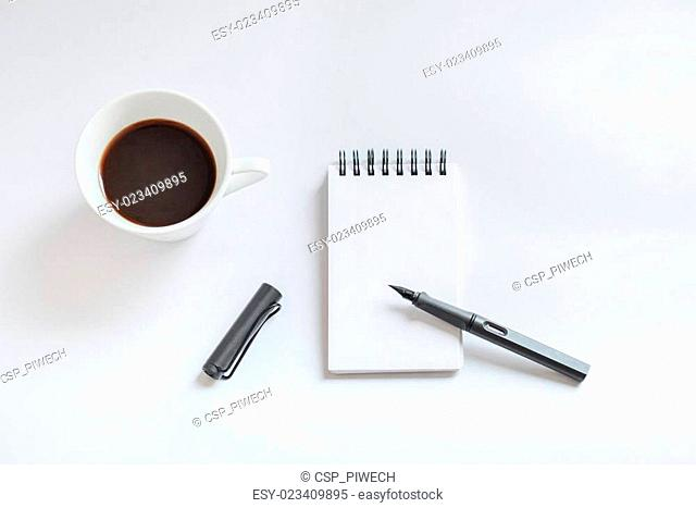 Coffee cup, spiral notebook and pen on white background