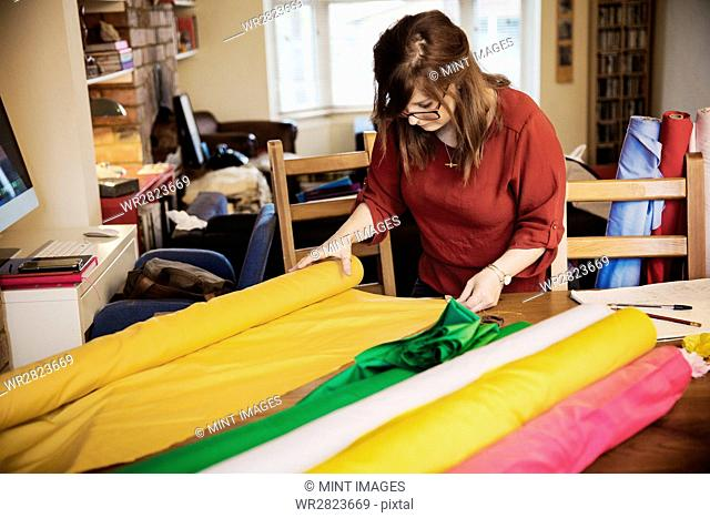 A woman choosing fabric from bolts of brightly coloured material on a tabletop in a workroom