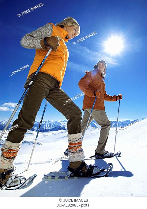 Low angle view of couple snowshoeing with ski poles