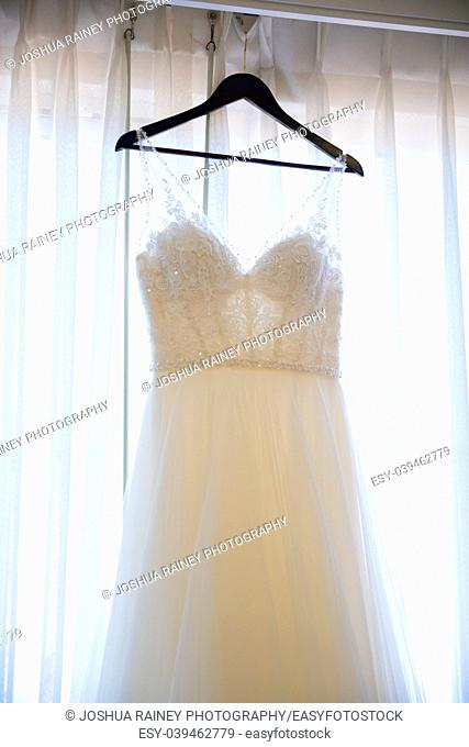 Wedding dress of the bride hanging against a curtain with strong backlight before she dresses for the ceremony