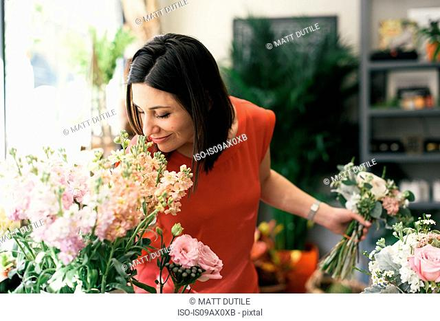 Florist smelling flowers in flower shop