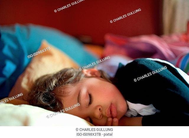 Young girl asleep on bed