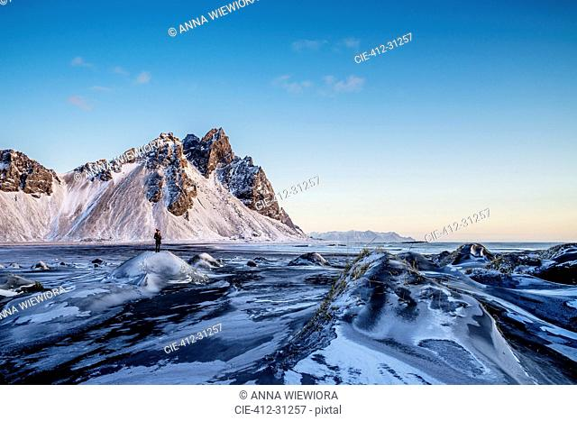 Woman standing among remote, icy landscape, Hofn, Iceland