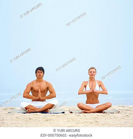 Portrait of a man and a woman meditating together on the beach