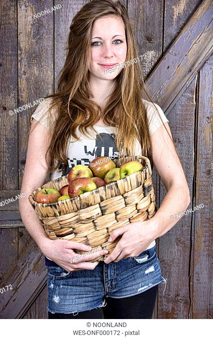 Germany, Portrait of teenage girl holding basket with organic apples, smiling