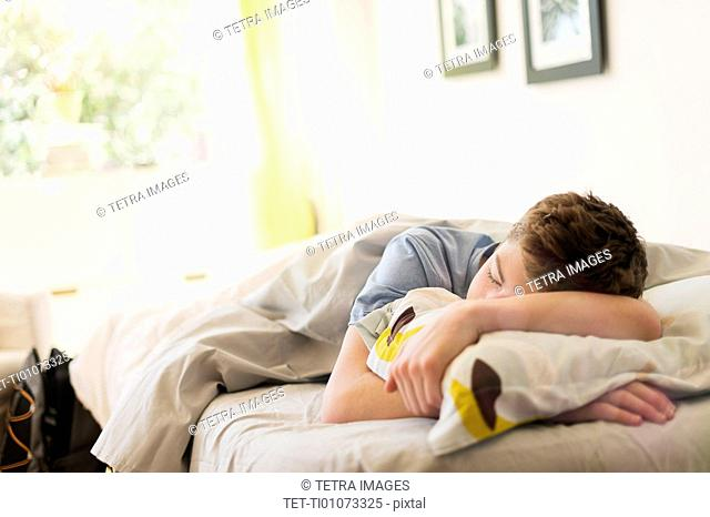 Teenage boy (16-17) sleeping in bed