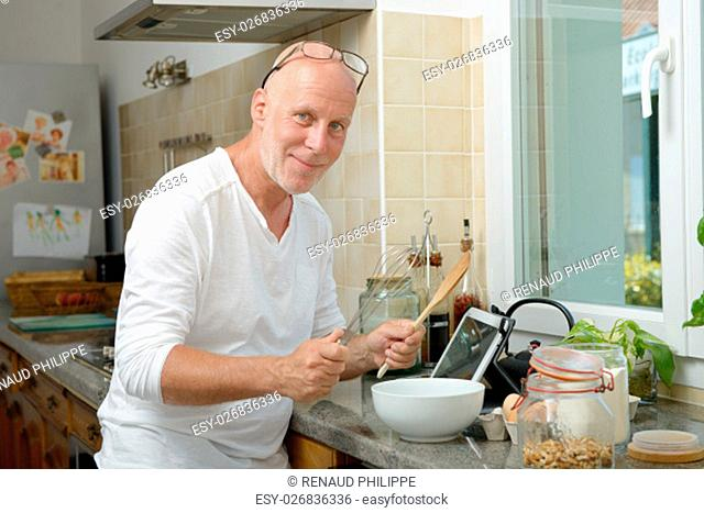 a mature man smiling in the kitchen
