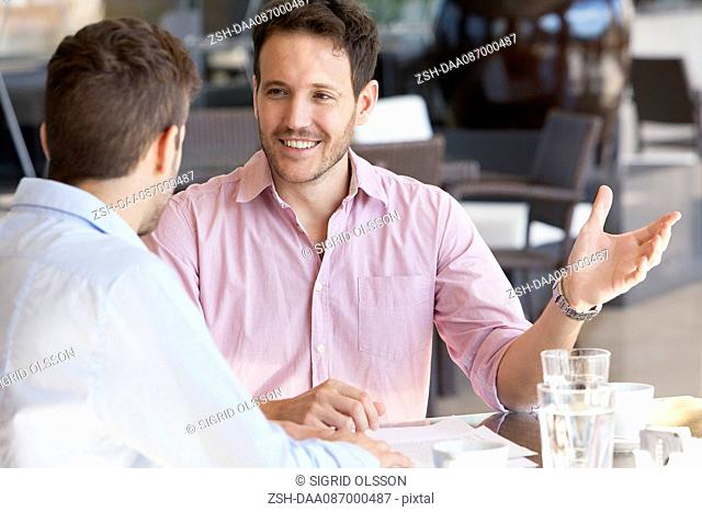 Business partners discussing work over coffee