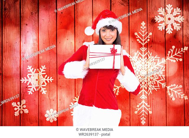 Portrait of woman in santa costume holding a gift