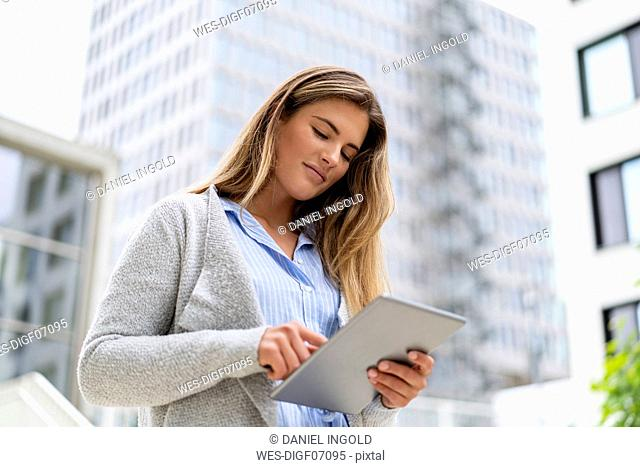 Portrait of young businesswoman using tablet, office buildings in the background