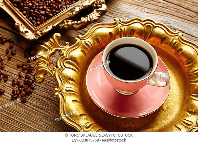 Coffee cup and beans on vintage golden tray in wooden old table
