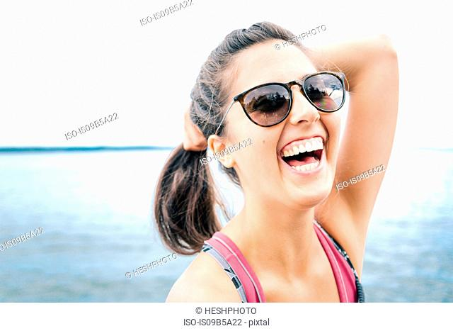 Young woman wearing sunglasses laughing by sea, Maine, USA