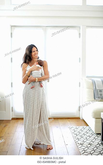 Portrait of mother, holding newborn baby boy, smiling
