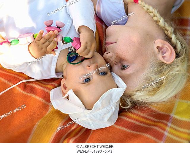 Girl playing with baby girl on blanket