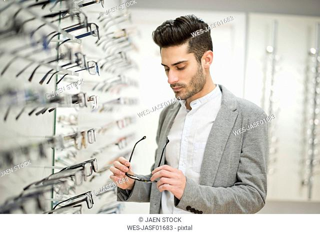 Young man looking for glasses at the optician's