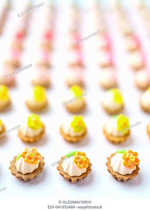 A lot of artificial cupcakes on white surface with shallow depth of field background