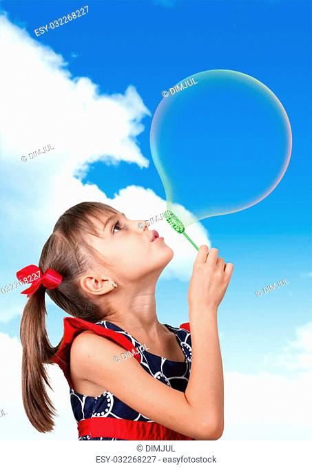 Portrait of funny child girl blowing big soap bubble on blue sky background