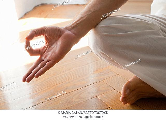 Close view of man's hand practicing yoga, sitting in the lotus position