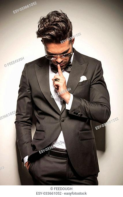 Elegant young business man holding one finger to his mouth whole looking down