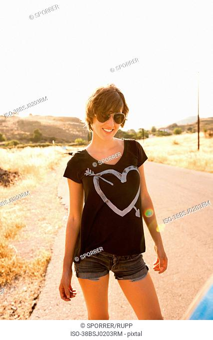 Smiling woman standing on rural road