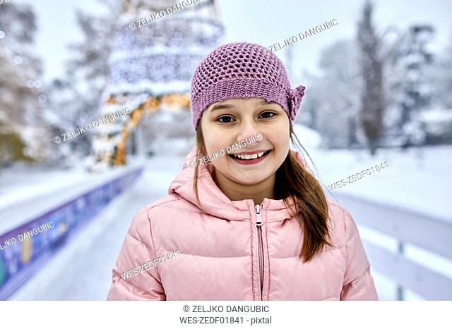 Portrait of a girl, wearing wooly hat, having fun ice skating on the ice rink