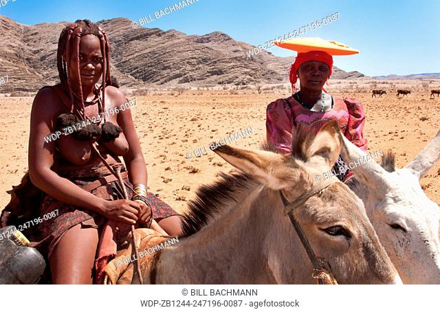 Namibia Africa Northern Desert colorful Herero tribe woman and Himba woman riding mules herding goats in Tomakas in Puros Conservancy remote farming