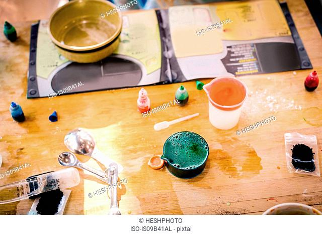 Child's messy chemistry set science experiment on table with instructions