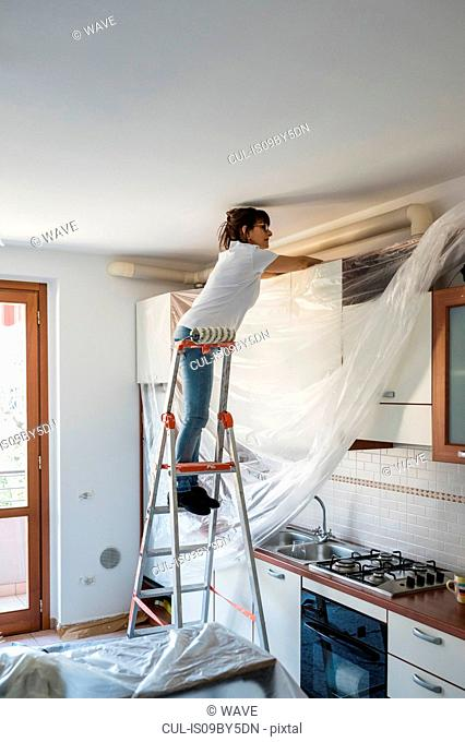 Senior woman on stepladder covering kitchen cabinets with plastic