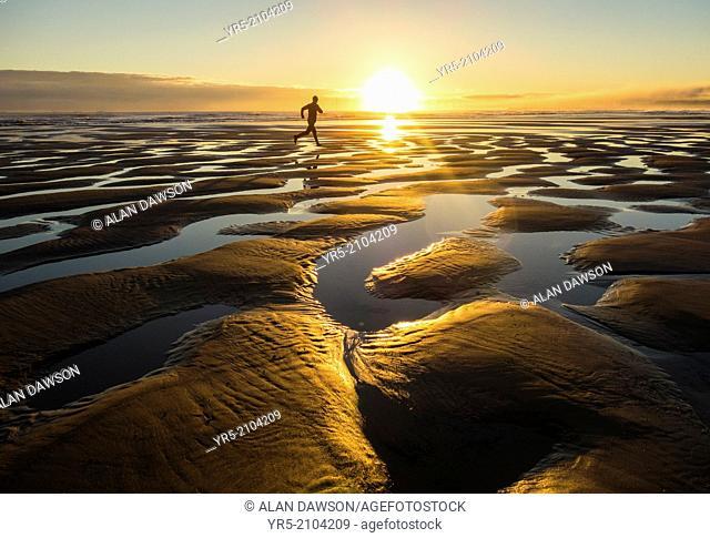 Jogger on beach at sunrise. Seaton Carew near Hartlepool, north east England, United Kingdom