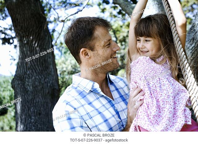 Close-up of a mid adult man pushing his daughter on a rope swing