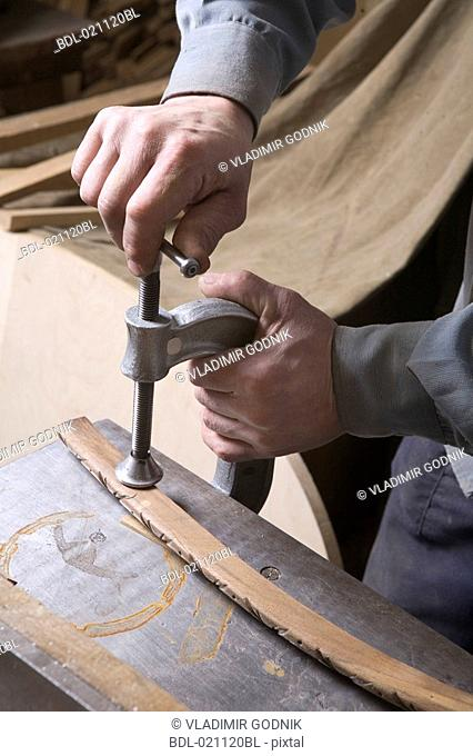 close-up of carpenter fixing piece of wood with hand-vice