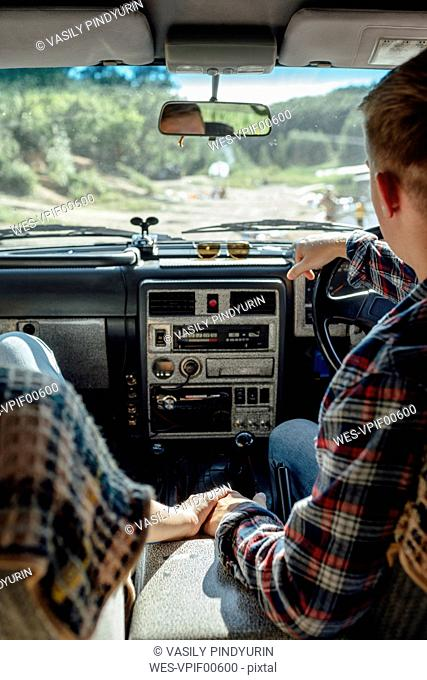 Romantic couple doing road trip, holding hands in car