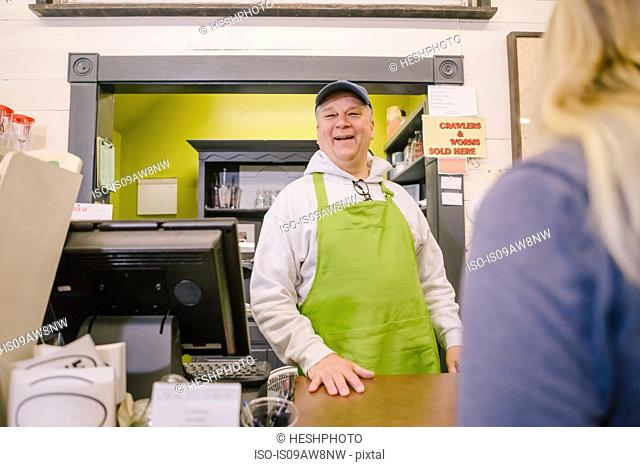 Owner in general store serving customer at counter