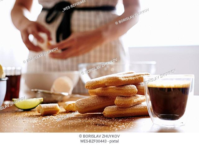 Glass of fresh coffee and heap of ladyfingers lying on table for preparing Tiramisu