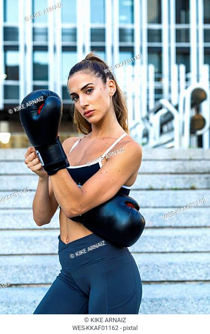 Portrait of sportive young woman putting on boxing gloves in the city