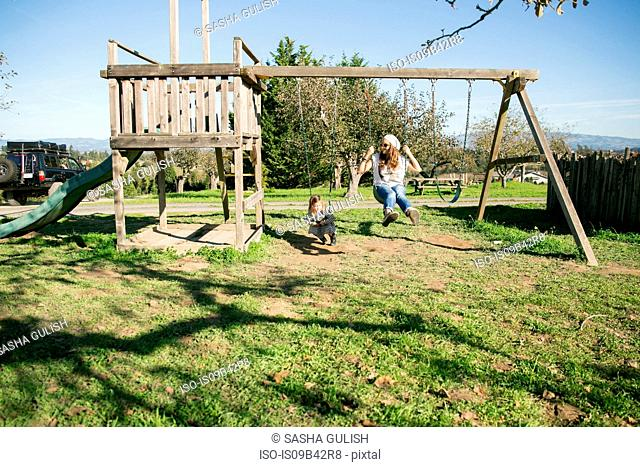 Mid adult woman and daughter sitting on swings in park