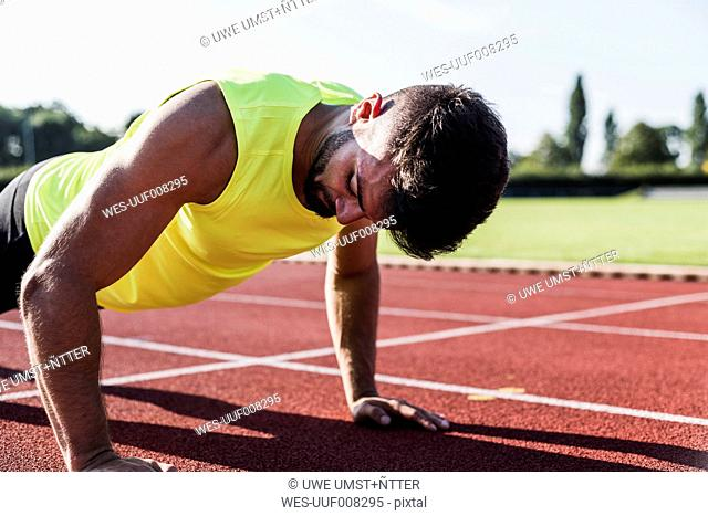 Athlete doing pushu-ups on tartan track