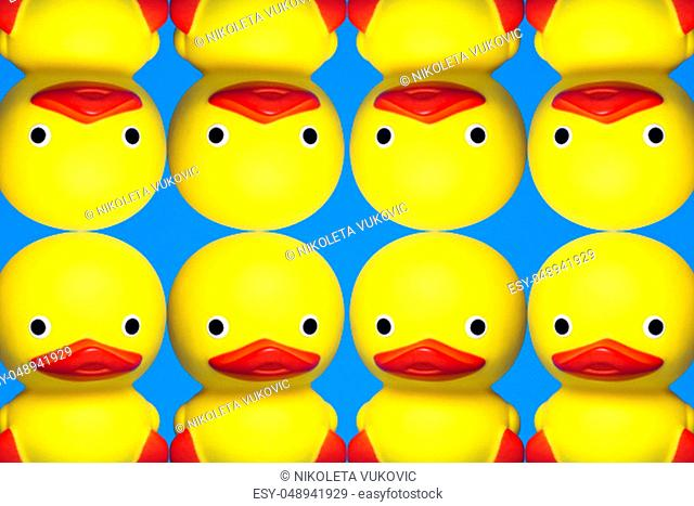 Eight yellow bath duck toys are in symmetry on blue background